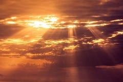 Sunset sky with light rays. Beautiful orange sunset sky with light rays going through clouds stock images