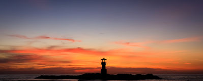 Sunset sky and a lighthouse silhouette Stock Images