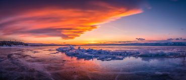 Sunset sky with natural breaking ice over frozen water on Lake Baikal, Siberia, Russia.  stock photography