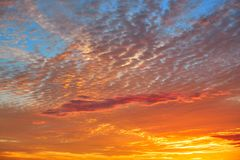 Sunset sky with orange clouds over blue royalty free stock images