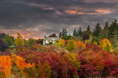 Sunset Sky over Farm House in Rural Oregon. Sunset sky over farm house with vibrant colored maple trees in rural Oregon in fall season Royalty Free Stock Image