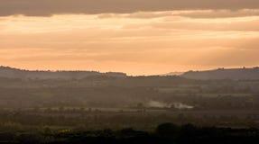 Sunset sky over a smoky Warwickshire landscape. Orange sunset sky over a hazy landscape with smoke, in Warwickshire, England Stock Photo