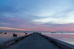 Sunset sky with port and  silhouette of small fishing boats. Stock Image