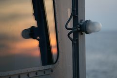 Sunset sky Reflect on the navy ship`s window. Sunset sky Reflect on the navy ship`s bullet prove window. on the windows there`s a light blue Royalty Free Stock Photography