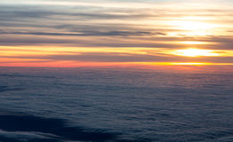 Sunset in sky view from plane flying over sea of clouds Stock Images