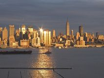Sunset Skyline. A tugboat pulls a barge along the Hudson River as the sunset reflects off the New York City skyline stock images