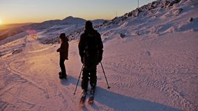 Sunset Slope Skier Snowboarder Beautiful Winter Panorama Slowmotion. Slowmotion footage of a skier and snowboarder riding the slope during a beautiful sunset stock video