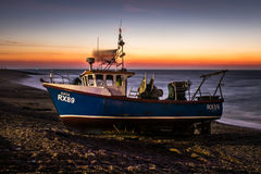 Before sunset small commercial fishing boat waiting to be launched from Hastings' beach. Stock Image