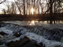 Sunset. On the small river waterfall Stock Photography