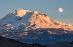 Sunset on snow capped mountain with moon Royalty Free Stock Photos