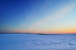 Sunset on a snowy field. Snowfield under the clear sky at sunset Stock Images