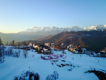Sunset in the snowy mountains and buildings. Aerial, Rosa Khutor Stock Photo