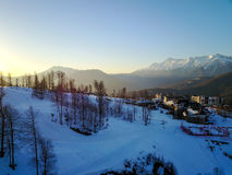 Sunset in the snowy mountains and buildings. Aerial, Rosa Khutor Royalty Free Stock Photo