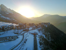 Sunset in the snowy mountains and buildings. Aerial, Rosa Khutor Stock Images