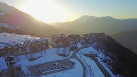 Sunset in the snowy mountains and buildings. Aerial, Rosa Khutor. Sochi stock footage