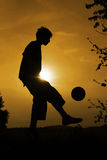 Sunset soccer. Silhouette of a boy how plays soccer in the sunset Stock Photos