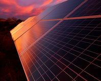 Sunset on Solar Panels. A glowing sunset is reflected in the panels of solar array composed of photovoltaic panels. Located in New Mexico Stock Photos