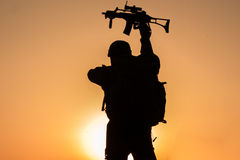 Sunset of soldier crouched in uniform. Beautiful sunset of soldier crouched in uniform holding his riffle high up Royalty Free Stock Photos