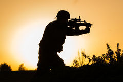 Sunset of soldier in uniform. Beautiful sunset of soldier crouched in uniform holding his riffle high up stock images