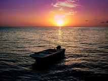 Sunset somewhere in the world. With a small fishing boat Stock Photography
