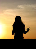 Sunset Song. Silhouette of a woman singing and enjoying sunset stock image
