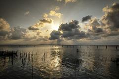 Sunset in Songkhla lake,Thailand. Sunset background with fishing equipment on the lake Royalty Free Stock Photography