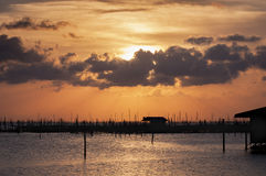 Sunset in Songkhla lake,Thailand. Silhouette fishing house and fishing equipment at sunset time on the lake beautiful sky background Stock Photo