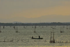 Sunset in Songkhla lake,Thailand. Silhouette people and boat  at sunset background with fishing equipment on the lake Royalty Free Stock Photo