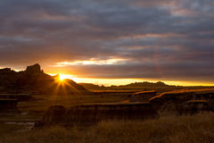 Sunset in the South Dakota Badlands. Sun rays give the badlands landscape a golden glow at sunset Stock Photos