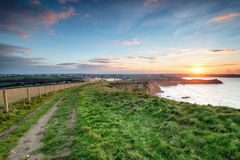 Sunset on the South West Coast Path in Cornwall. Stunning sunset on the South West Coast Path as it approaches Porth on the outskirts of Newquay in Cornwall Royalty Free Stock Image