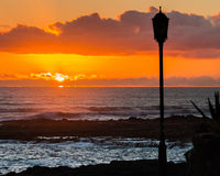 Sunset in Spain. Ocean and orange cloudy sky in Fuerteventura at sunset with silhouette of a street lamppost in the foreground Royalty Free Stock Photography