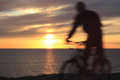 Sunset and sportsmen. Sunset, biker, sky and sea Stock Photos