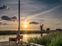 Sunset at St Benet`s Level Drainage Mill. The River Thurne Norfolk Broads. Mooring in foreground and the drainage mill on the opposite bank. Sun setting pink Royalty Free Stock Image