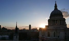 Sunset and St. Pauls Cathedral. The sun setting behind St. Pauls cathedral with the London Skyline in silhouette Stock Photo