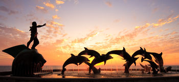 Sunset with statue of Dolphins. Statues of Dolphins in fountain in front of bright orange sunset over the ocean royalty free stock photos