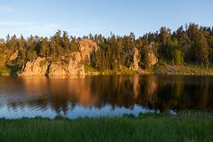 Sunset at Stockade Lake. Golden sunshine in the late afternoon shines on a quartz rock formation and creates a soft reflection at Stockade Lake in Custer State royalty free stock photography