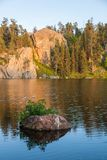 Sunset at Stockade Lake. A small rock with green plants growing off of it and surrounded by lake water with a golden glow of late afternoon sunshine lighting up royalty free stock images