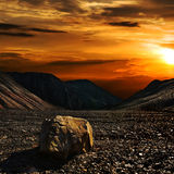 Sunset with the stone. Stone on the hill of old mine of Donbass stock images