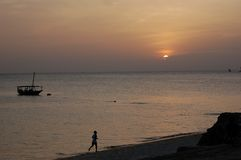 Sunset in Stone Town. One man run on the beach at sunset. Stone Town, Zanzibar, Tanzania stock image