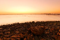 Sunset, stones and shoreline. Stones at shoreline during sunset near Bahrain harbour Royalty Free Stock Photo