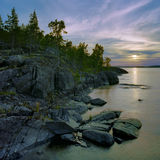 Sunset at stony shore of Ladoga lake, Russia Stock Photos