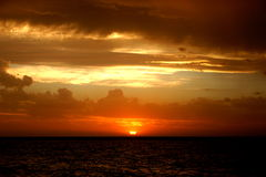 SUNSET AT STRADBROKE. A beautiful orange sunset at Stradbroke Island, in Queensland, Australia. Dramatic skies and both dark and orange lit ocean. Endless Stock Images