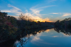 Sunset by a Stream. Sun setting over a small pond during the Autumn months Royalty Free Stock Image