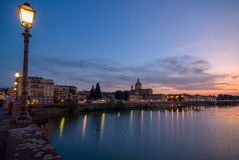 Sunset and streetlamp at river arno stock photography