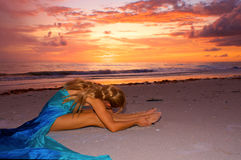 Sunset stretch on beach. A long haired blonde woman is sitting on beach watching the sunset as she stretches her back and holds her ankles Stock Images