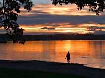Sunset Stroll. A lone woman strolls the shores of Sylvan lake, Alberta at sunset stock image