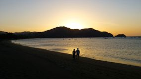 Sunset Stroll in Costa Rica. Silhouette of couple walking on a beach in Costa Rica stock photos