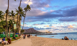 Sunset Stroll. Waikiki Beach, , Oahu, Hawaii, USA - August 17, 2015: Locals and tourists flock to stoll or relax on the sand to watch the sunset every evening on stock photo