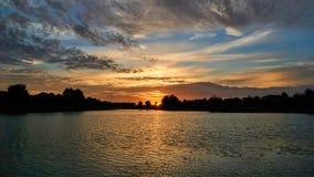 Sunrise over still pond in suburban neighborhood stock photography