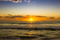 Sunrise. At the horizon with clouds on the Ocean Stock Photos